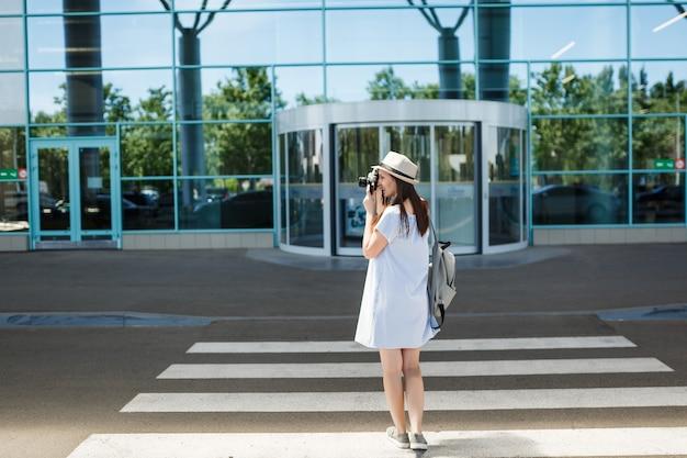 Молодой путешественник турист женщина с рюкзаком фотографирует на ретро старинный фотоаппарат на пешеходном переходе в международном аэропорту