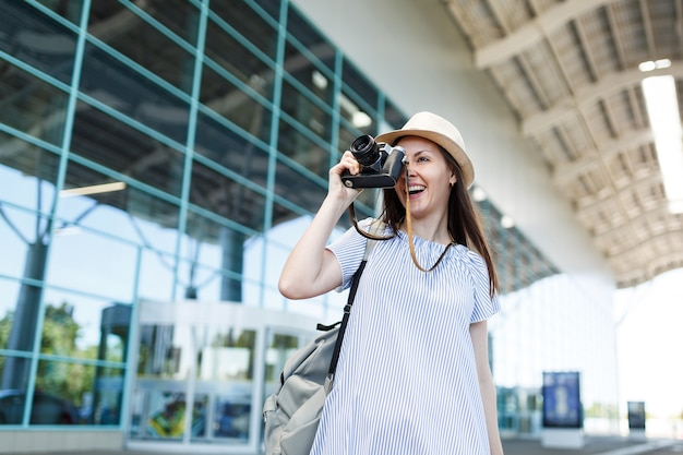 Young traveler tourist woman with backpack taking pictures on retro vintage photo camera at international airport
