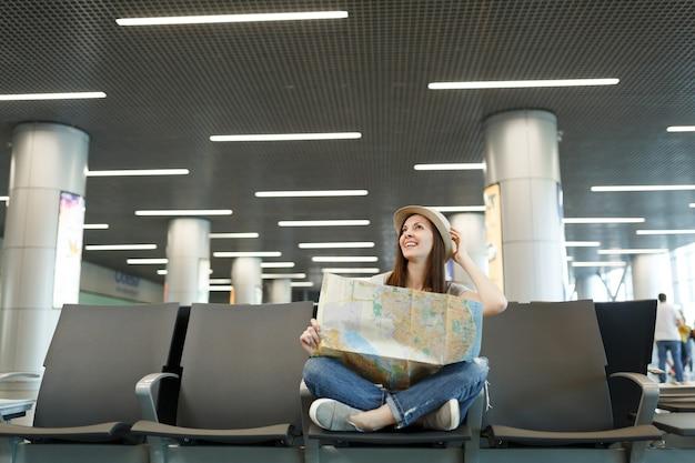 종이지도를 들고, 모자를 곧게 펴고, 국제 공항 로비 홀에서 기다리고 교차 다리를 가진 젊은 여행자 관광 여자