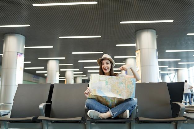 종이지도에 검지 손가락을 가리키는 교차 다리를 가진 젊은 여행자 관광 여자, 국제 공항 로비 홀에서 기다리고