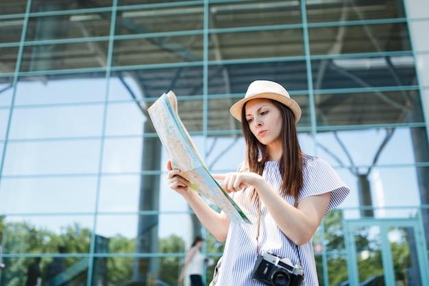 国際空港の紙の地図でレトロなビンテージ写真カメラ検索ルートを持つ若い旅行者観光客の女性