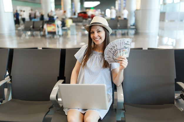 Young traveler tourist woman working on laptop holding bundle of dollars, cash money, waiting in lobby hall at international airport