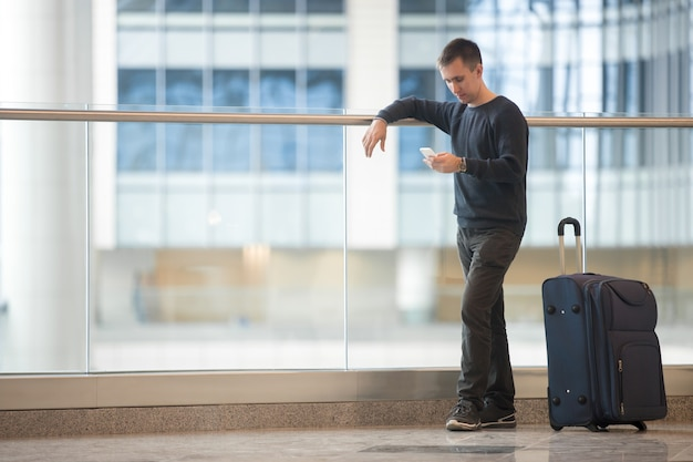 Giovane viaggiatore utilizzando smartphone in aeroporto