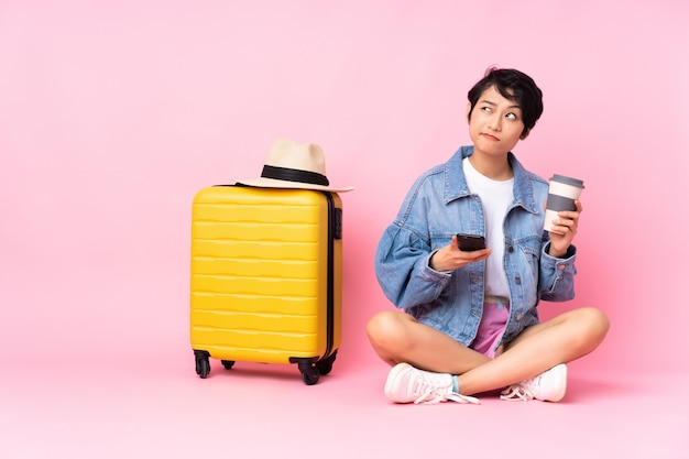 Young traveler vietnamese woman with suitcase sitting on the floor over isolated pink wall holding coffee to take away and a mobile while thinking something