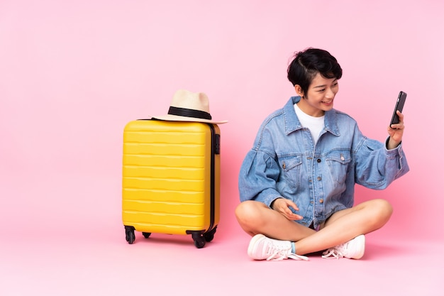 Young traveler vietnamese woman with suitcase sitting on the floor over isolated pink wall making a selfie