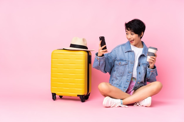 Young traveler vietnamese woman with suitcase sitting on the floor over pink wall holding coffee to take away and a mobile