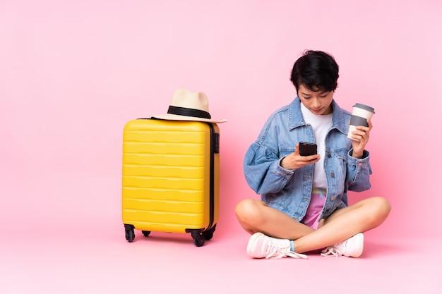 Молодой путешественник вьетнамская женщина с чемоданом сидит на полу над изолированной розовой стеной, держа кофе на вынос и мобильный