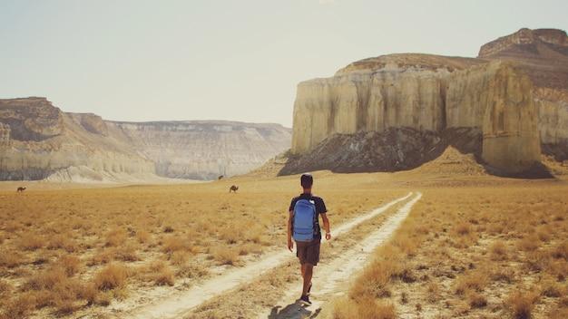 A young traveler walks along a path in a mountainous area