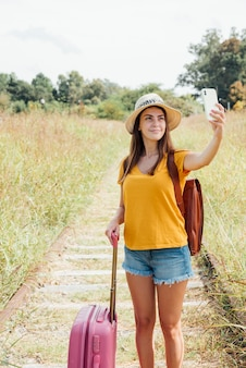 Young traveler with luggage taking a selfie