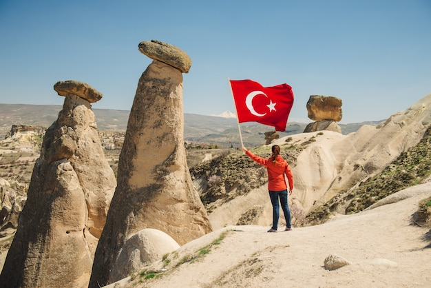 Young traveler with turkish flag in cappadocia desert landscape