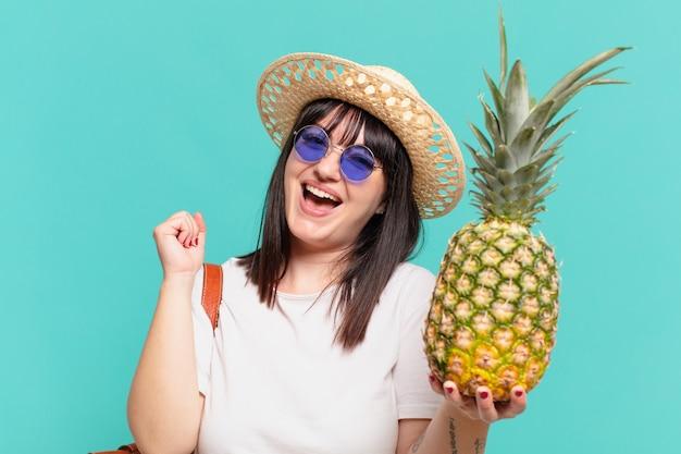 Молодой путешественник женщина празднует успешную победу и держит ананас