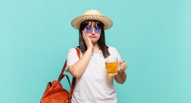 面倒で退屈で退屈な仕事をした後、退屈、欲求不満、眠気を感じ、手で顔を抱えている若い旅行者の女性 Premium写真