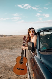 Young traveler woman having fun with the guitar in the jeep 4x4 car making a wanderlust vacation at sunset