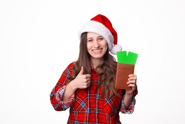 Молодая женщина-путешественница в рождественской шляпе держит паспортные билеты, показывая большой палец вверх на белом фоне