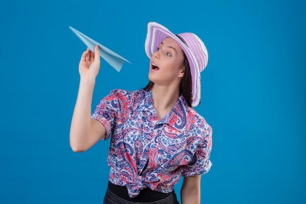Молодая женщина путешественника в шляпе лета держа бумажный самолетик шаловливый и счастливый над голубой стеной