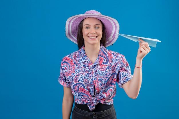 Молодая женщина путешественника в шляпе лета держа бумажный самолетик положительный и счастливый усмехаясь жизнерадостно над голубой стеной