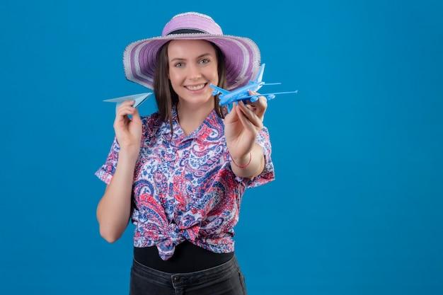 Молодая женщина-путешественница в летней шляпе держит бумажные и игрушечные самолетики, играя с ними позитивно и счастливо, стоя на синем фоне
