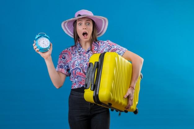青い背景上の恐怖の間違い式のための恥でショックを受けたカメラを見て目覚まし時計を保持している黄色のスーツケースを持って夏帽子立っている若い旅行者女性