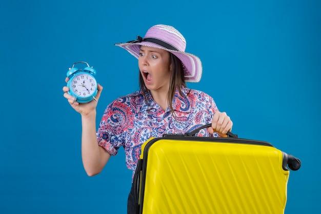それを見て目覚まし時計を保持している黄色のスーツケースと夏の帽子立っている若い旅行者女性