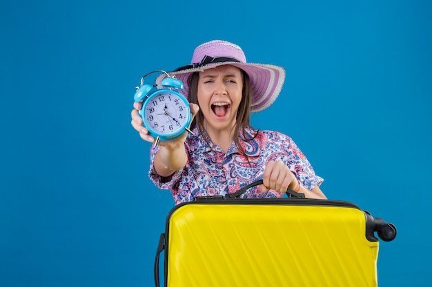 目覚まし時計がイライラしてイライラした青い壁を越えて怒りで叫んでいる黄色のスーツケースと夏の帽子の若い旅行者女性