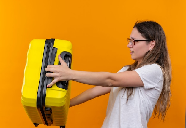オレンジ色の壁の上に立って不機嫌そうに見える誰かに彼女のスーツケースを与える白いtシャツの若い旅行者の女性