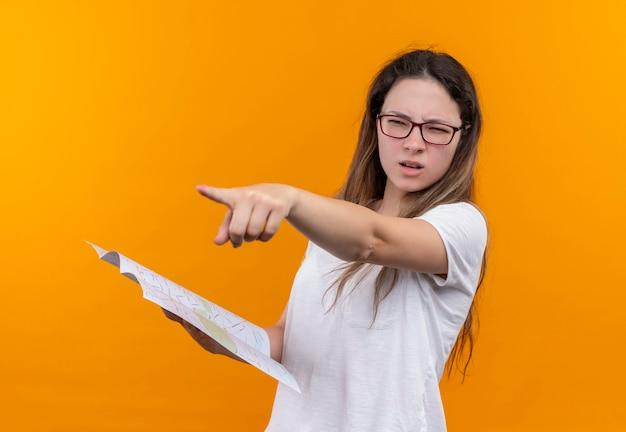 オレンジ色の壁の上に立っている指で正しい方向を指している地図を保持している白いtシャツの若い旅行者の女性