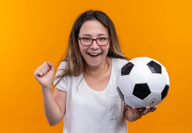Молодая женщина-путешественница в белой футболке держит футбольный мяч, выглядит взволнованной и счастливой, сжимая кулак, стоя на оранжевой стене