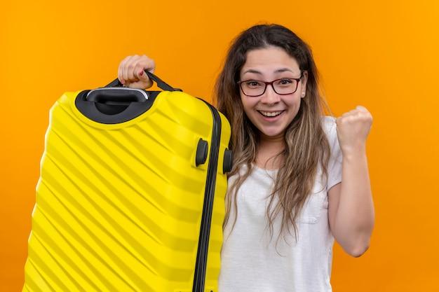 オレンジ色の壁の上に立って興奮して幸せな握りこぶしを握ってスーツケースを保持している白いtシャツの若い旅行者の女性