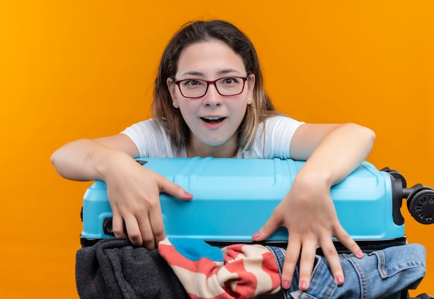 Молодая путешественница в белой футболке держит чемодан, полный одежды, выглядит удивленным с улыбкой на лице, стоящей над оранжевой стеной