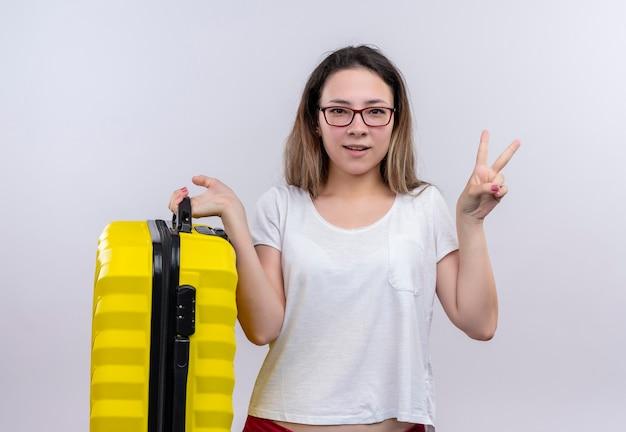 白い壁の上に立っている勝利のサインを示す幸せでポジティブなスーツケースを保持している白いtシャツの若い旅行者の女性