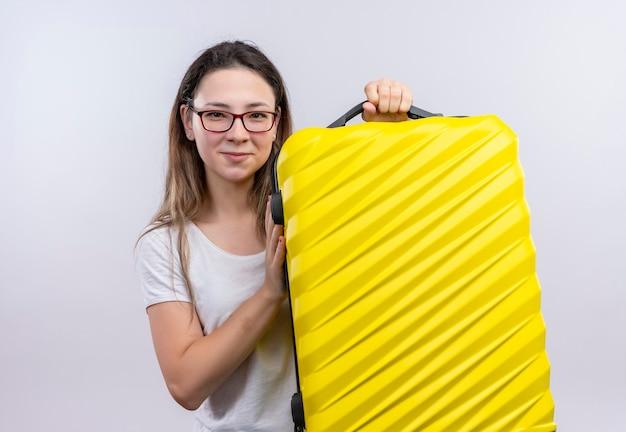 白い壁の上に立って幸せで前向きな笑顔のスーツケースを保持している白いtシャツの若い旅行者の女性