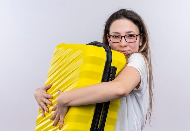 Молодая путешественница в белой футболке держит чемодан, обнимает чемодан, улыбается позитивно и счастливо, стоя над белой стеной
