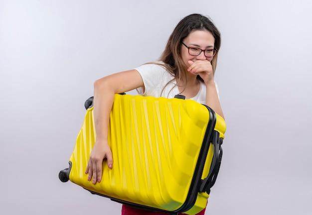 白い壁の上に幸せで前向きに立って笑っているスーツケースを保持している白いtシャツの若い旅行者の女性
