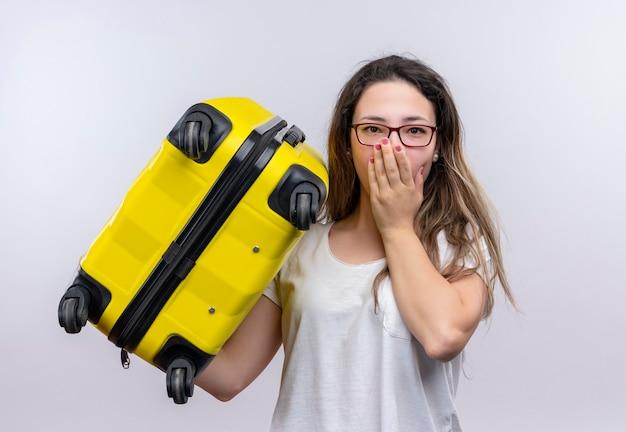 白い壁の上に立っている手で口を覆って驚いて驚いたように見えるスーツケースを保持している白いtシャツの若い旅行者の女性