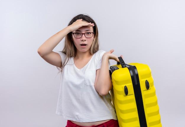 Молодая путешественница в белой футболке с чемоданом выглядит изумленной и удивленной, стоя у белой стены