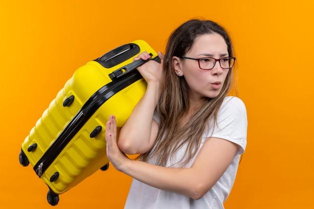 オレンジ色の壁の上に立って不機嫌そうな脇を見てスーツケースを保持している白いtシャツの若い旅行者の女性