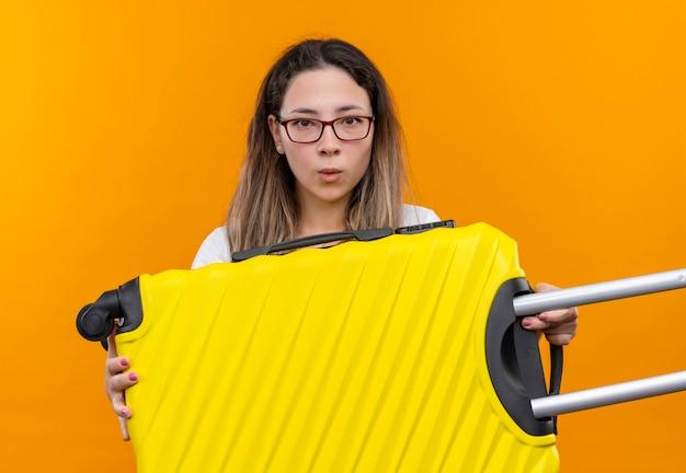 オレンジ色の壁の上に立って混乱して非常に心配そうに見えるスーツケースを保持している白いtシャツの若い旅行者の女性