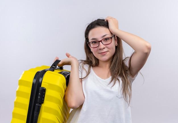 Молодая путешественница в белой футболке держит чемодан, смущенно улыбаясь, стоя над белой стеной