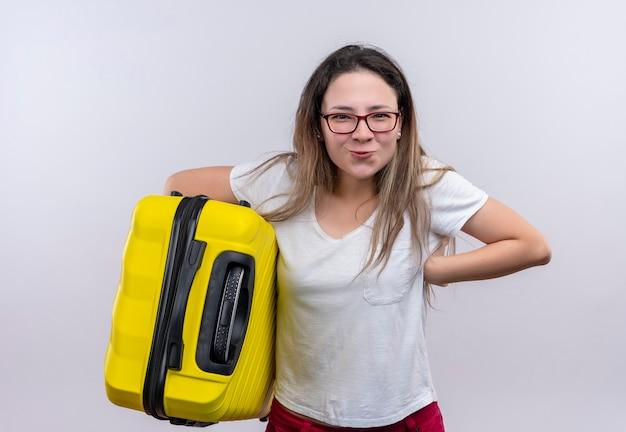 Молодой путешественник женщина в белой футболке держит чемодан, выглядит радостным и счастливым, улыбаясь, стоя над белой стеной
