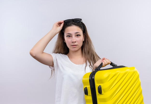 Молодая путешественница в белой футболке держит чемодан с озадаченным видом, стоя у белой стены