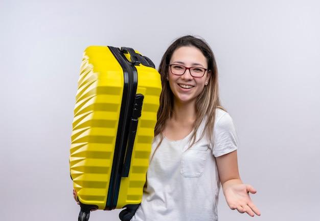 Молодая путешественница в белой футболке держит чемодан, весело улыбаясь, поднимая руку, стоя над белой стеной