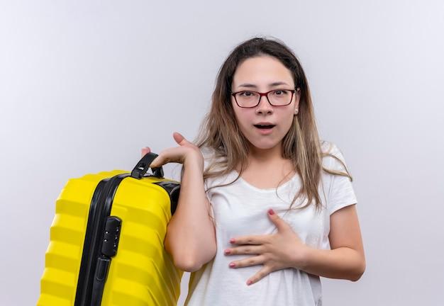 Молодая путешественница в белой футболке с чемоданом, выглядящая удивленной и пораженной, стоя над белой стеной
