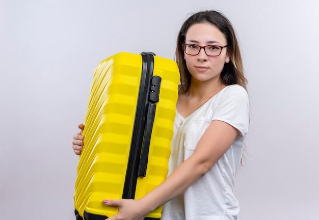 Молодой путешественник женщина в белой футболке держит чемодан
