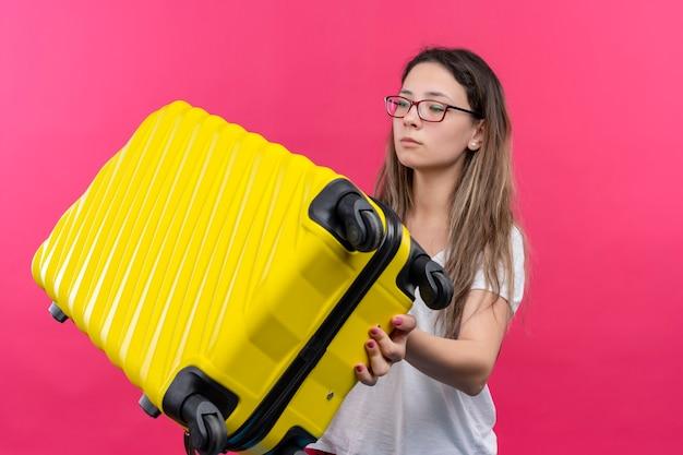 ピンクの壁の上に立っている深刻な顔で脇を見て旅行スーツケースを保持している白いtシャツの若い旅行者の女性
