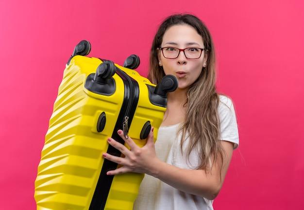 ピンクの壁の上に立って驚いて驚いて見える旅行スーツケースを保持している白いtシャツの若い旅行者の女性