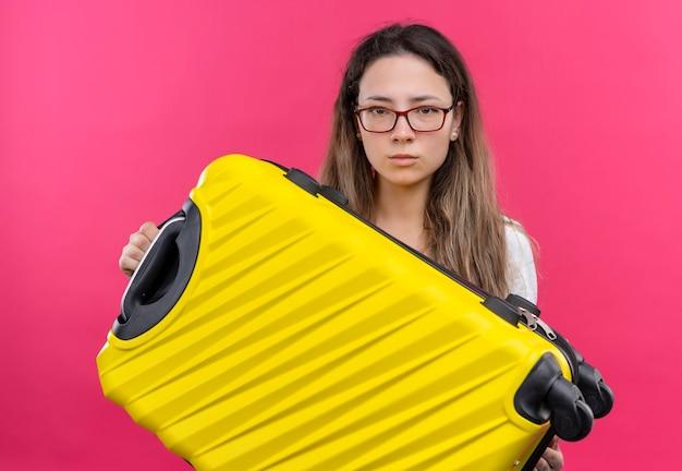 ピンクの壁の上に立っている真剣な表情で探している旅行スーツケースを保持している白いtシャツの若い旅行者の女性