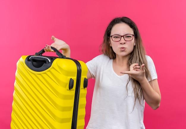 ピンクの壁の上に立ってイライラして見える人差し指でそれを指している旅行スーツケースを保持している白いtシャツの若い旅行者の女性
