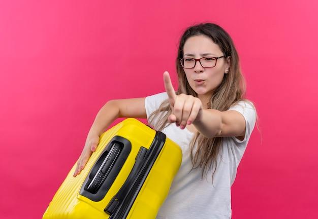 ピンクの壁の上に立っている深刻な顔と人差し指の警告を示す旅行スーツケースを保持している白いtシャツの若い旅行者の女性