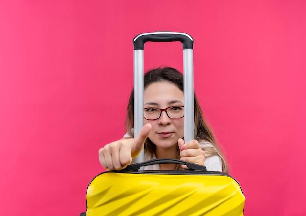 ピンクの壁の上に立って自信を持って見ている親指を示す旅行スーツケースを保持している白いtシャツの若い旅行者の女性