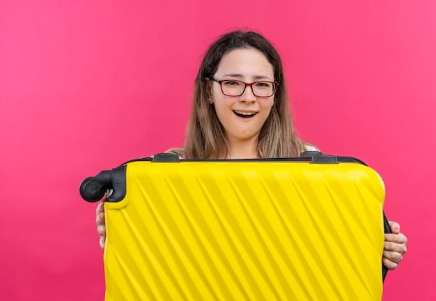 ピンクの壁の上に元気に立って笑顔の旅行スーツケースを保持している白いtシャツの若い旅行者の女性